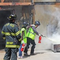 community emergency response team members extinguishing a fire with a fire extinguisher